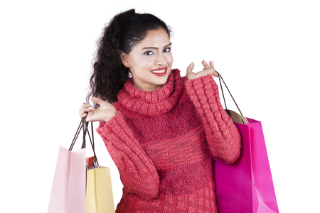 clothes shopping: Portrait of happy indian woman wearing sweater while carrying shopping bags and smiling at the camera in the studio