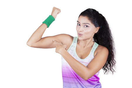 strong women: Portrait of beautiful indian woman wearing sportswear and pointing at her bicep, isolated on white