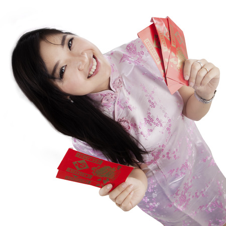 view girl: High angle view of cheerful chinese girl holding chinese envelope, isolated on white