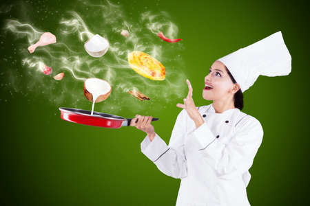 asian flavors: Portrait of indian chef cooking with magic while using frying pan and wearing uniform Stock Photo