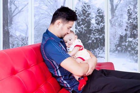 month: Photo of young father sitting on the sofa while holding his baby for making a good relation