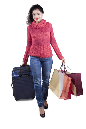carrying girl: Pretty indian woman walking in the studio while wearing warm clothes and carrying shopping bags with suitcase
