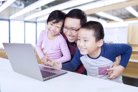 asian adult: Young teacher and his students using laptop in the classroom for studying and having fun