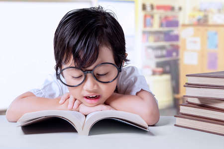 kid book: Portrait of pretty female kindergarten student sitting in the classroom while reading textbooks