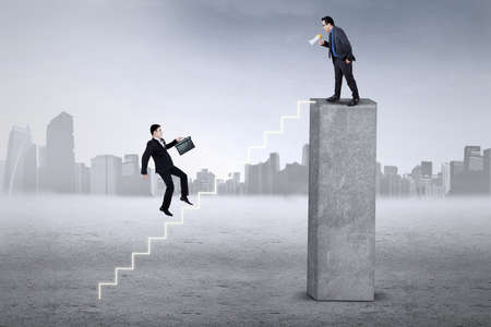 finance director: Businessman hurry up stepping the stairs after called by his leader from the top