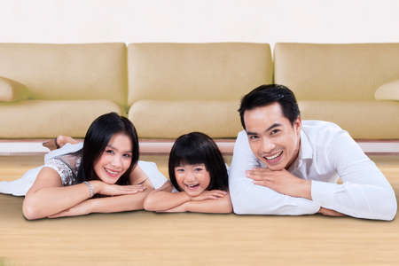 family sofa: Photo of cheerful family lying on the floor while smiling at the camera near the sofa at home