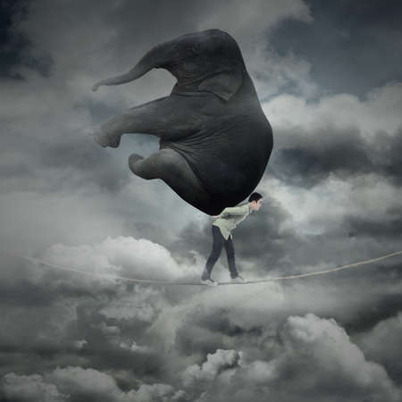 heavy weight: Portrait of businessman carrying heavy elephant while walking on the rope