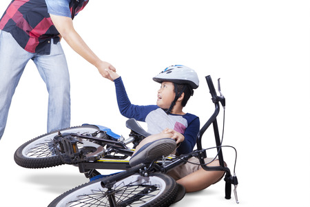 get help: Little child learn to ride a bike and falling off, crying and get help from his father