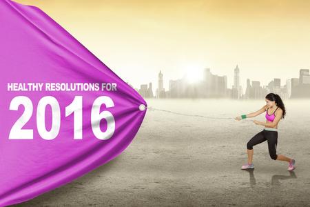 Mooie Indiase vrouw het dragen van sportkleding en trekt tekst van gezonde resolutie voor 2016 met een grote vlag Stockfoto