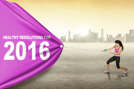 fitness goal: Pretty indian woman wearing sportswear and pulls text of healthy resolution for 2016 with a big flag
