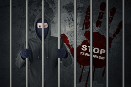 syria peace: Concept of stop terrorism: Male terrorist standing in the jail while wearing mask
