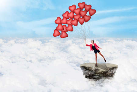 above clouds: Happy young woman holding red balloons above the clouds Stock Photo