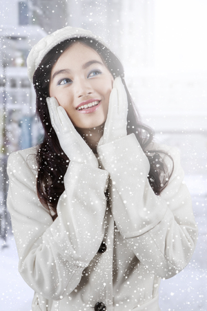 cute girl smiling: Image of beautiful teenage girl with beauty pose and wearing winter coat in snowy day at the city