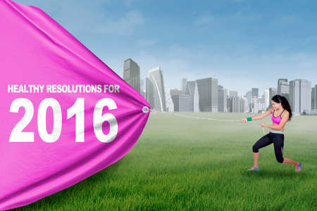 lifestyle outdoors: Portrait of attractive indian woman pulling a text of healthy resolution for 2016 while wearing sportswear at field