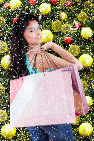 woman standing: Pretty indian woman smiling at the camera while holding shopping bags with christmas tree decorations