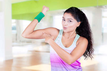gym workout: Image of happy indian woman pointing her bicep while wearing sportswear after workout at gym