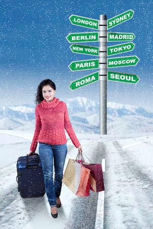 femme valise: Jolie jeune femme indienne avec des v�tements d'hiver, en marchant sur la route tout en transportant des sacs et valise avec le signe de route du lieu de destination de vacances