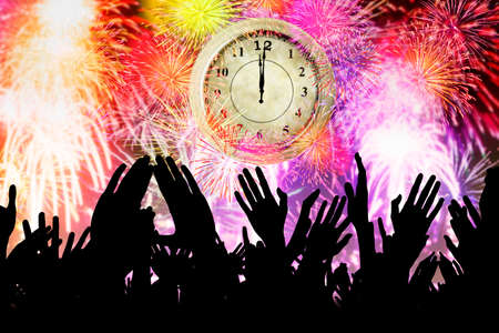 new years eve party: Silhouette of crowd people hands with an old clock and the colorful fireworks. New year concept Stock Photo