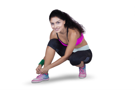 shoes woman: Portrait of pretty indian young woman tying her shoelaces while wearing sportswear, isolated on white background