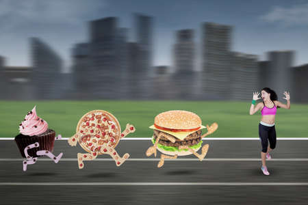 avoid: Image of indian young woman chased by junk food and run at field while wearing sportswear