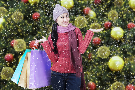 shopper: Image of pretty female shopper wearing winter clothes and holding shopping bags with christmas decoration background