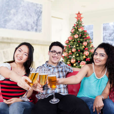 young friends: Portrait of cheerful multi ethnic people making a champagne toast while celebrate christmas day at home