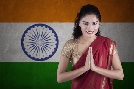 woman clothes: Portrait of indian woman wearing traditional clothes with greeting gesture in front of Indian flag Stock Photo