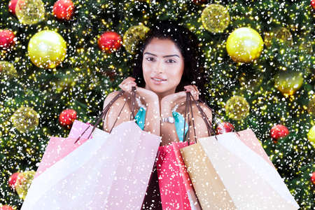 christmas girl: Portrait of indian young woman holding christmas shopping bags with christmas tree decoration Stock Photo