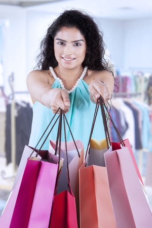 woman standing: Attractive indian woman with casual clothes, giving shopping bags at the camera, shot in the shopping mall