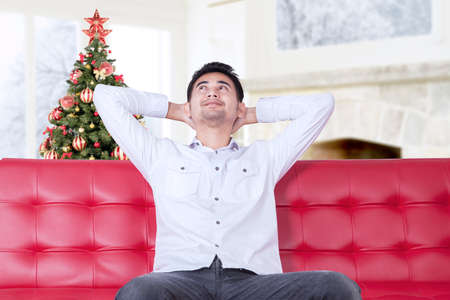 rest and relaxation: Happy young man relaxing at home while sitting on the couch and daydreaming with christmas tree on the back