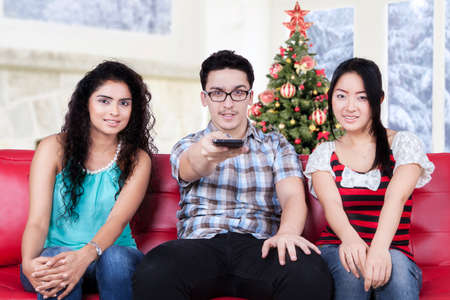 christmas movies: Group of three multi ethnic people watching tv at home and change the channel by using smartphone, shot with christmas tree on the back