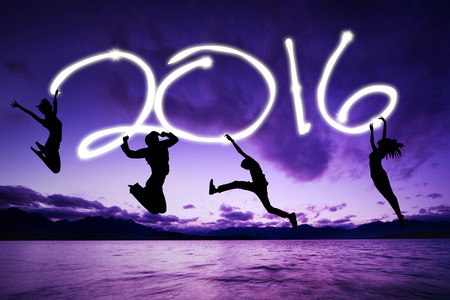 four people: Silhouette of four people jumping on the beach while celebrating new year of 2016