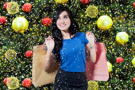 shopper: Happy female shopper carrying shopping bags and standing in front of christmas decoration background