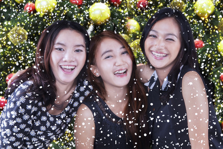 girl studying: Portrait of three happy teenage girls laughing together with ornaments and a christmas tree background
