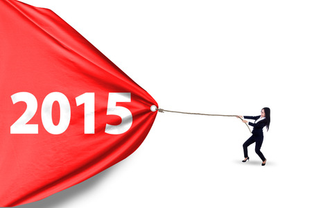 dragging: Young businesswoman dragging a banner with number 2015 in studio, isolated over white background