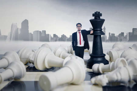 business rival: Businessman winning chess game on cityscape background