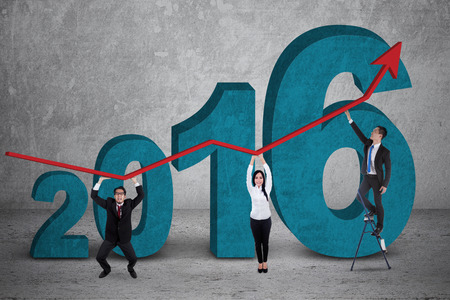 new years resolution: Image of three young business people lifting an upward arrow with numbers 2016