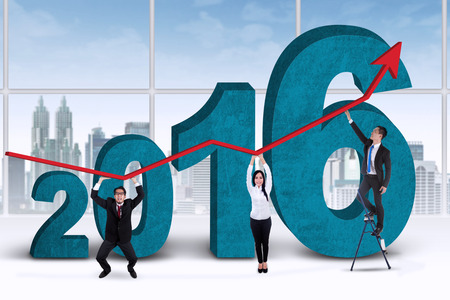 stockmarket chart: Three young business people lifting upward arrow in the office with numbers 2016