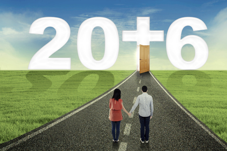 jesus standing: Happy couple standing on the road while holding hands and looking at numbers 2016 with a cross Stock Photo