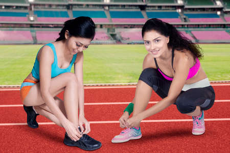 shoelace: Two sporty woman doing workout at stadium and tying shoelaces
