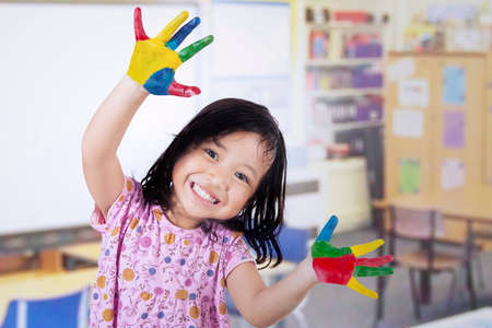 infant school: Smiling little girl with hands painted in colorful paints on classroom