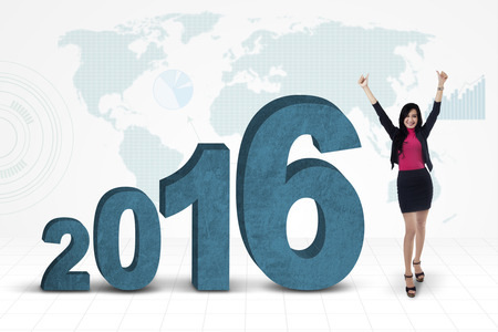 profit celebration: Picture of cheerful female worker celebrating her success with numbers 2016 and world map