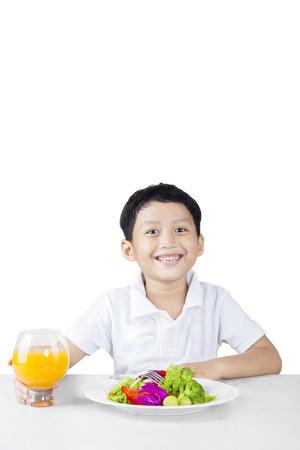 tomando jugo: Pequeño niño sonriente comiendo una ensalada de verduras y jugo de naranja, aislado en fondo blanco Foto de archivo