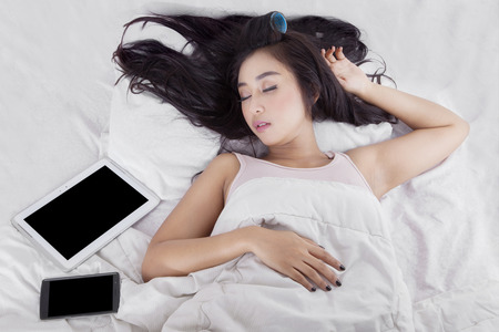 Beauty woman sleeping near to her smartphone and digital tablet on the bed