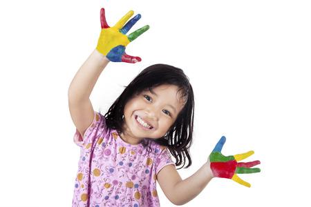 Bonne petite fille montrant ses mains peintes dans les peintures colorées, isolé sur fond blanc