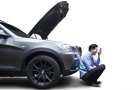 car isolated: Angry young businessman using phone by broken down car, isolated on white background