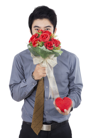 give: Portrait of happy young man with flowers and a gift - isolated on white background