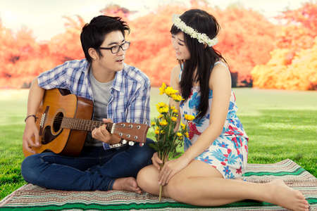 boyfriend: Image of handsome young man sitting on the autumn park with his girlfriend while playing guitar