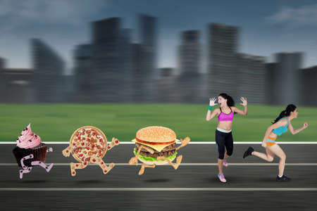 chased: Image of two young woman chased by junk food and run at field while wearing sportswear