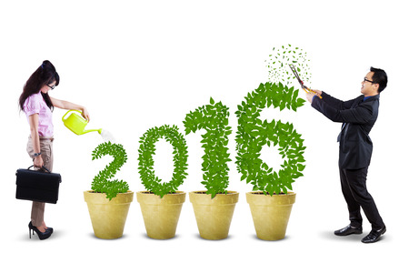 nurture: Two young businesspeople nurture tree shaped numbers 2016 on the pot, isolated on white background